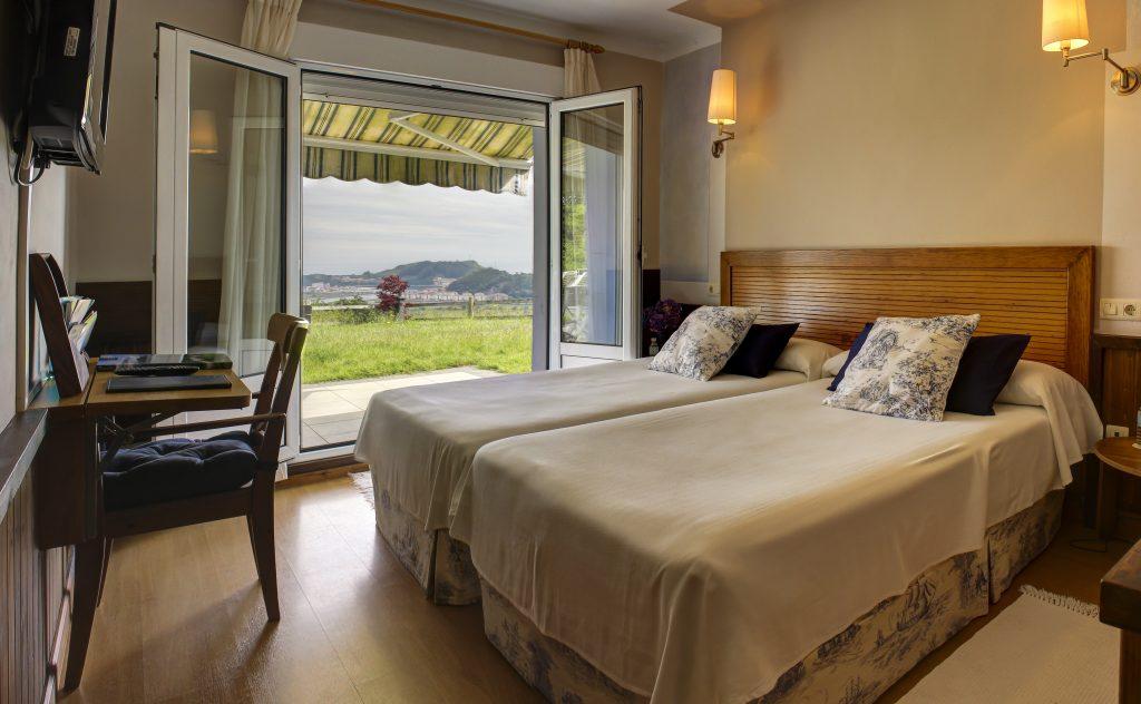 habitación doble con dos camas salida al jardín y vistas al mar