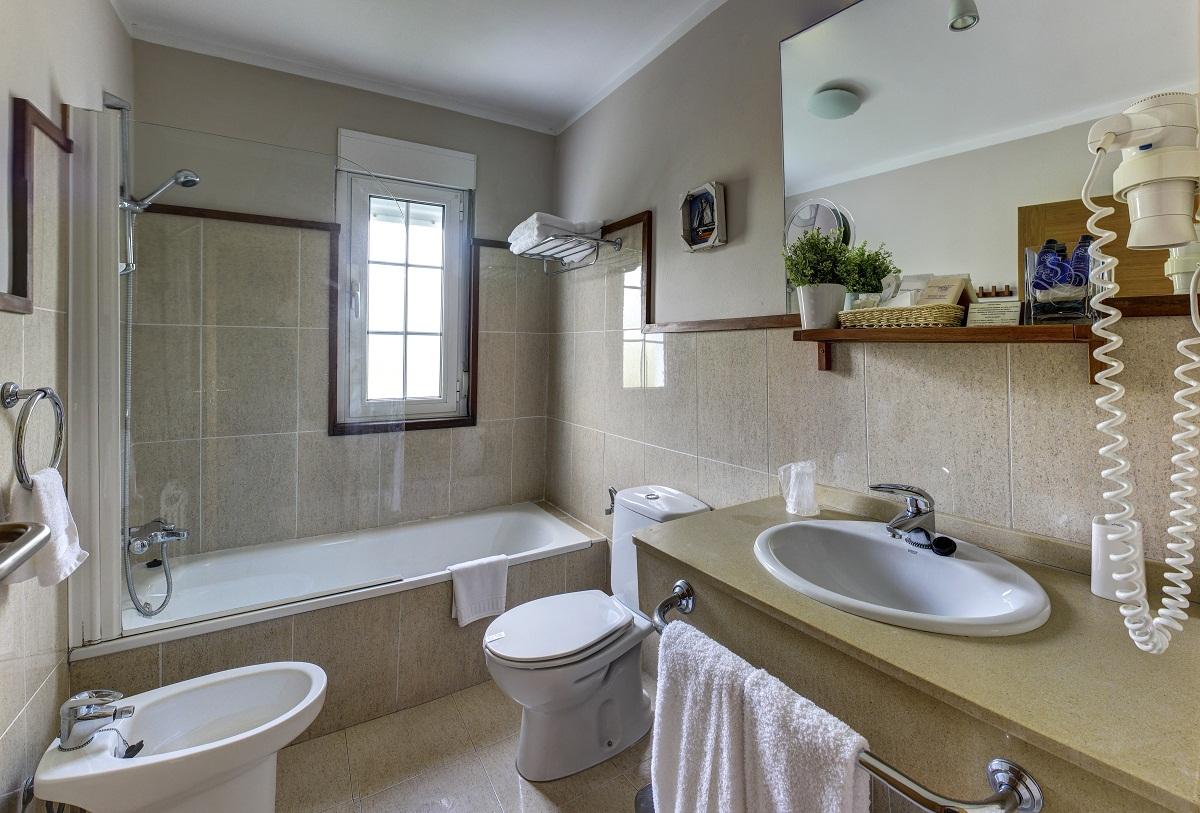 Baño con bañera, secador de pelo y productos de acogida del hotel Mirador del Sella