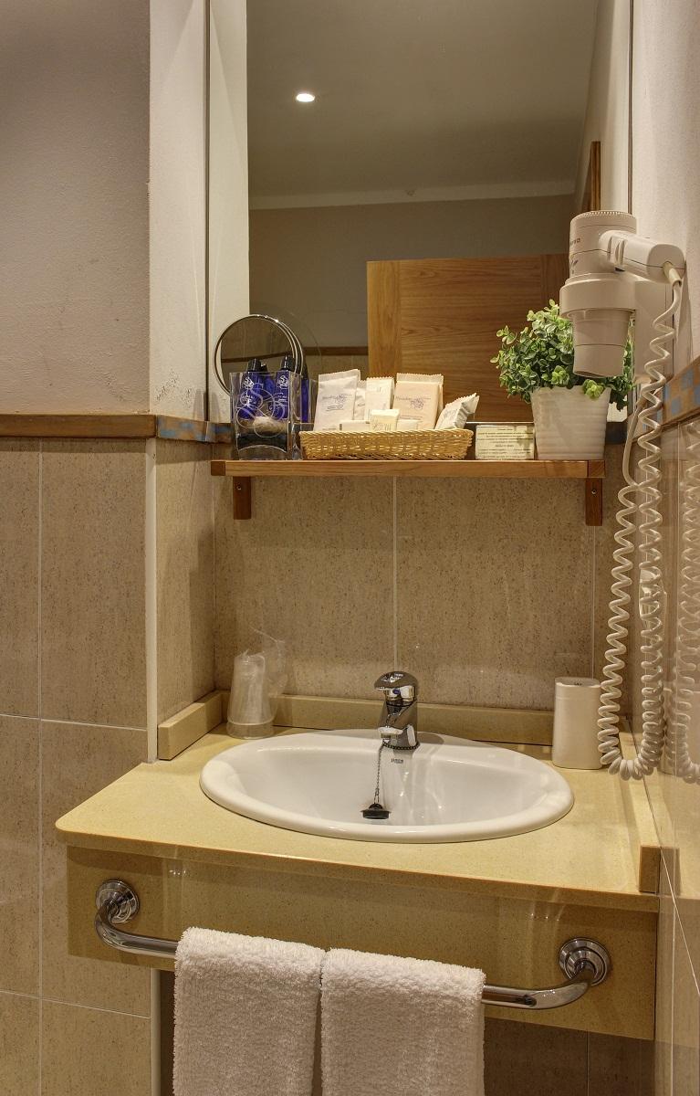 Detalle del lavabo con productos de acogida y secador de pelo